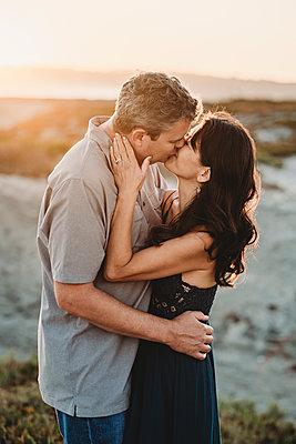 Husband and wife exchange romantic kiss at the Bach - p1166m2207851 by Cavan Images
