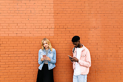 Young couple using smart phones against brick wall - p1192m2109922 by Hero Images