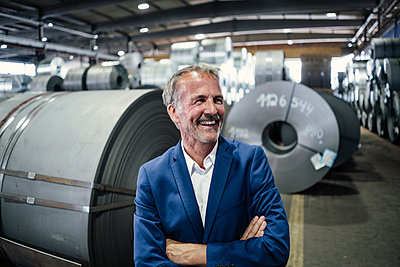 Happy businessman standing with arms crossed in steel mill - p300m2299024 by Gustafsson