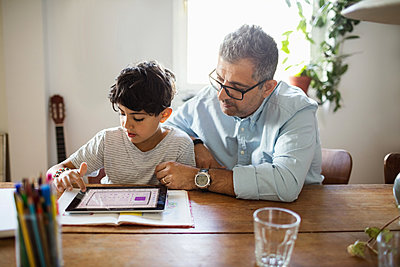 Father assisting son in using digital tablet at home - p426m1193013 by Maskot
