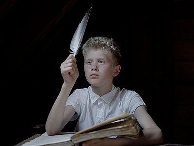 Boy with blond hair doing his homework - p945m1154600 by aurelia frey