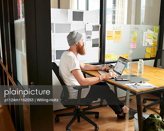Designer sitzt am Schreibtisch - p1124m1162053 von Willing-Holtz