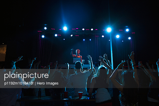Crowd cheering for DJ on stage at nightclub - p1192m1016410f by Hero Images