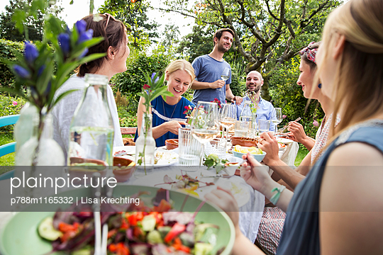 Gemeinsam essen auf einer Gartenparty - p788m1165332 von Lisa Krechting
