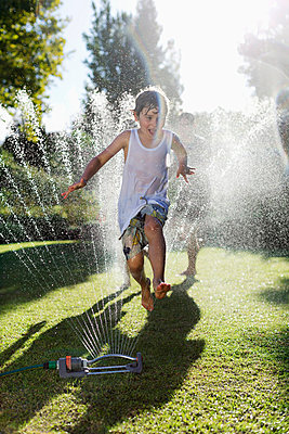 Boy playing in sprinkler in backyard - p1023m820172f by Paul Bradbury