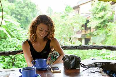 Caucasian girl  smiling with coffee mug on a terrace bar in Ubud, Bali - p1166m2093895 by Cavan Images