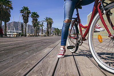 Leg of young woman sitting on bicycle - p300m1130079f von Andrés Benitez
