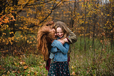 Mother and daughter hugging in wooded area, Lakefield, Ontario, Canada - p429m1408182 by Erin Lester