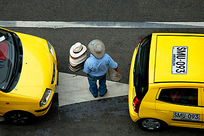 Medellin, Colombia, Street Vendor Selling Traditional Colombian Hats And Panama Hats In Between Parked Taxis, Aburra Valley, Antioquia, The Vendor Is Wearing A Colombian Hat Called A 'Sombrero Vuelitado' - p651m860478 by John Coletti photography