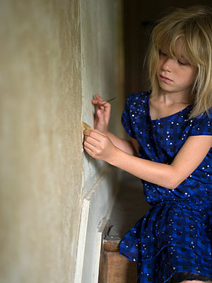 Girl ripping off flakes of wallpaper - p945m1465914 by aurelia frey