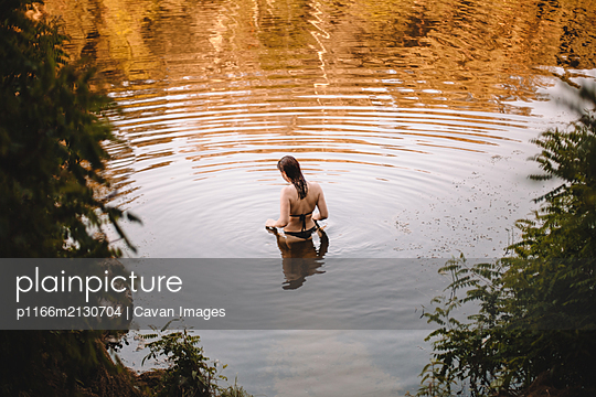 Sensual woman standing in lake in forest - p1166m2130704 by Cavan Images