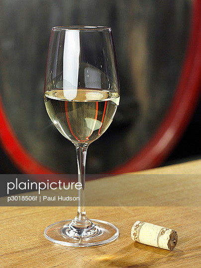 A glass of white wine with a cork next to it, still life