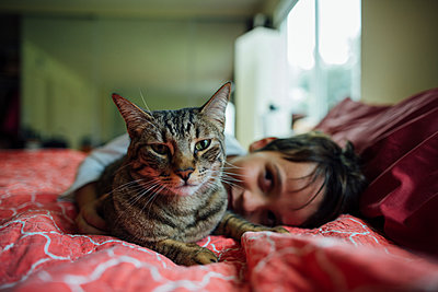Portrait of cat by boy on bed at home - p1166m1403102 by Cavan Images