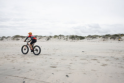 A mountain biker rides across the beach, South Africa - p1640m2244963 by Holly & John