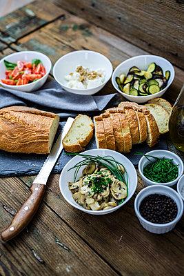 Bruschetta and various ingredients, bread, tomato, zucchini, cheese, ricotta, walnuts, mushroom, herbs, basil, chives - p300m1550222 by Giorgio Fochesato