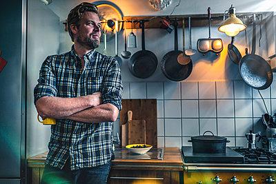 Man in kitchen at home looking sideways - p300m2132448 by Richárd Bellevue