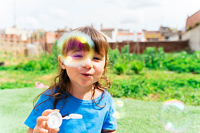 Portrait of happy little girl blowing soap bubbles in a park - p300m2188625 by Gemma Ferrando