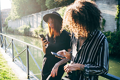 Couple using mobile phones while standing by railing against pond in park - p300m2206881 by Eugenio Marongiu