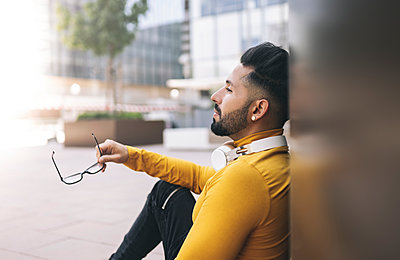 Man holding eyeglasses while leaning on wall - p300m2300073 von Jose Carlos Ichiro