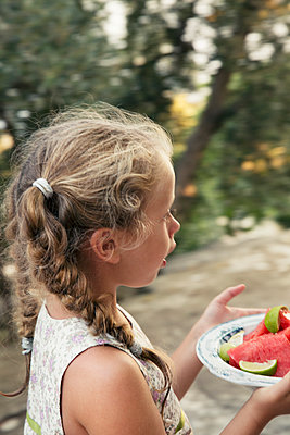 Girl carrying plate with watermelons - p972m1160339 by Idha Lindhag