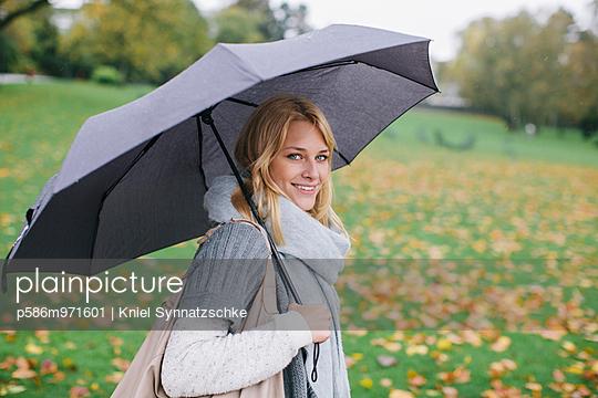Junge Frau mit Regenschirm im Park - p586m971601 von Kniel Synnatzschke