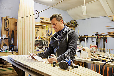 Man standing in a workshop with a wooden surf board, holding paper and pen.  - p1100m1220530 by Mint Images