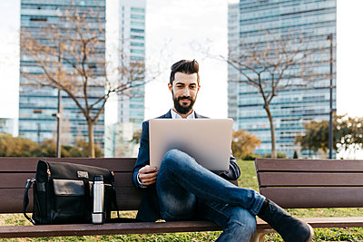 Businessman sitting on bench outside office building using laptop - p300m1563131 by Josep Rovirosa