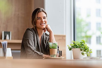 Young businesswoman in a cafe - p300m2114089 by Daniel Ingold
