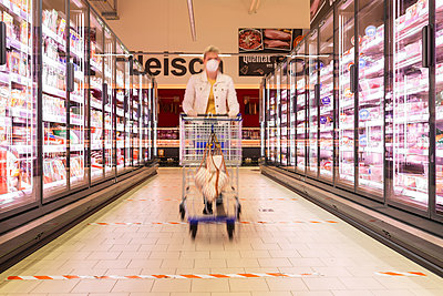 Young woman wearing mask pushing shopping cart at supermarket - p300m2225044 by Anke Scheibe