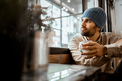 Mid adult man wearing knit hat with coffee cup looking through window in cafe - p300m2277384 by Rafa Cortés