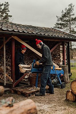 Senior couple chopping wood - p312m2191241 by Jennifer Nilsson