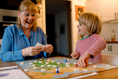 Cheerful grandmother and grandson playing board game at home - p426m2195295 by Maskot