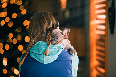 Girl carrying puppy indoors - p924m2090595 by Rebecca Nelson