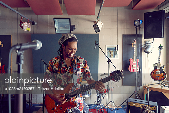 Male musician playing electric guitar in recording studio - p1023m2190257 by Trevor Adeline