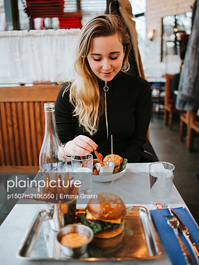 Young woman sits in fast food restaurant - p1507m2196550 by Emma Grann