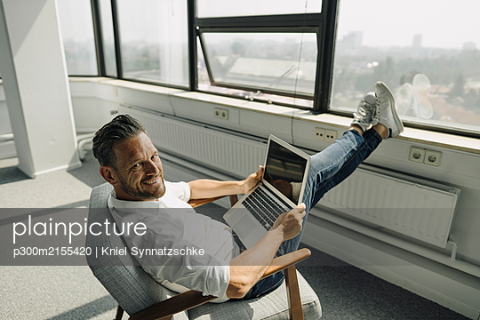 Portrait of smiling mature businessman using laptop in empty office - p300m2155420 by Kniel Synnatzschke