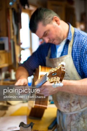 Guitar maker in his workshop - p300m2213861 by Tom Chance