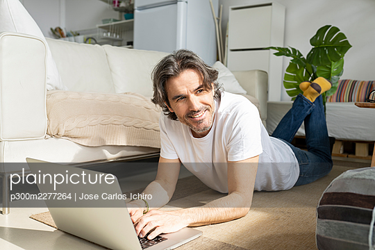 Thoughtful man with laptop looking away while lying on floor at home - p300m2277264 by Jose Carlos Ichiro