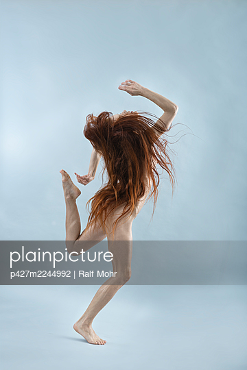 Naked woman with red hair makes dance steps - p427m2244992 by Ralf Mohr