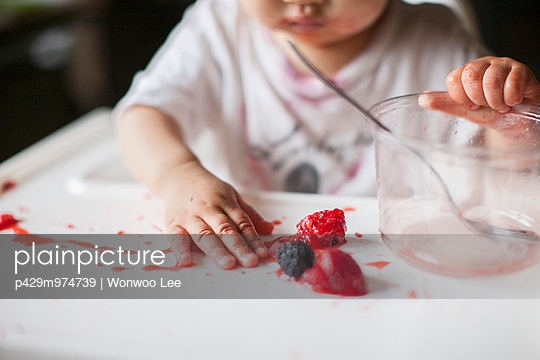 Cropped close up of one year old baby girl playing with fruit on highchair - p429m974739 by Wonwoo Lee