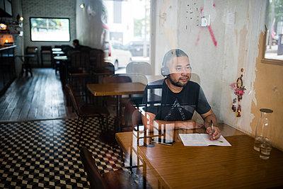 Asian man listening music on headphones - p1166m2131278 by Cavan Images