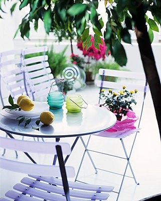 Hurricane candles and lemons on a patio table with folding chairs - p1183m996947 by Manduzio, Matteo