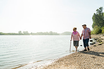 Germany, Ludwigshafen, senior couple walking hand in hand at riverside - p300m1068795f by Uwe Umstätter