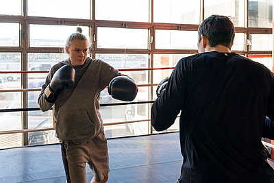 Female boxer sparring with her coach in gym - p300m2170823 by Vasily Pindyurin