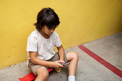Boy using mobile phone while sitting on skateboard against wall - p300m2203154 by Valentina Barreto
