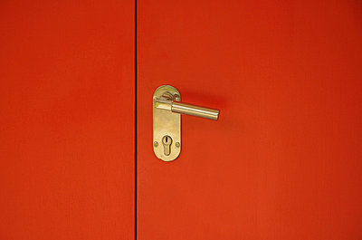 Detail of a gold door handle on a red door - p30118274f by Aron Jungermann