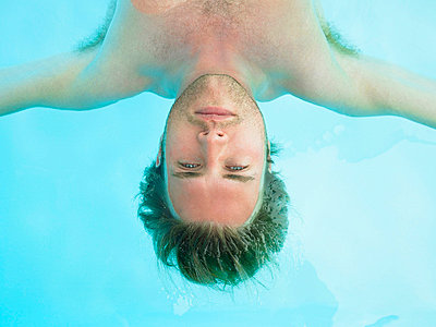 young man floating in water - p4297592f by Aurelie and Morgan David de Lossy