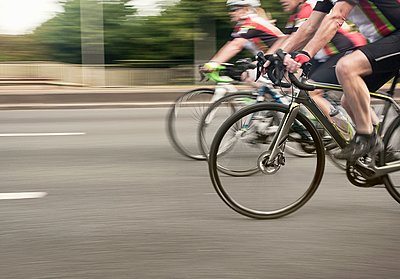 Neck down view of three cyclists speeding on urban road in racing cycle race - p429m1118531f by Seb Oliver