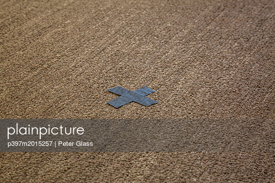 Silbernes X aus Klebeband auf einen Teppich geklebt - p397m2015257 von Peter Glass