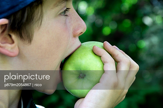 Boy biting into green apple - p879m2054867 by nico